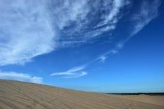 在沙丘的蓝色多云天空 免版税图库摄影
