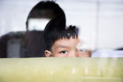 在沙发后的男孩皮在镜子屋子 库存图片