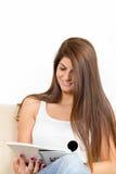 在沙发和微笑的女孩读书 库存照片