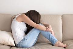 在沙发和拥抱膝盖的沮丧的青少年的开会 图库摄影