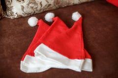 在沙发的三个圣诞老人帽子 新年家庭观念 免版税库存照片