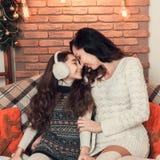 在沙发的两个可爱的女孩、母亲和女儿选址在Christma 图库摄影