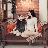 在沙发的两个愉快的女孩、母亲和女儿选址在圣诞节 免版税库存图片