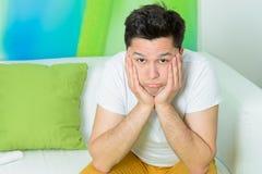 年轻在沙发的人疲倦的开会 免版税库存图片
