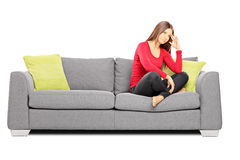 在沙发的哀伤的年轻女性开会 库存照片