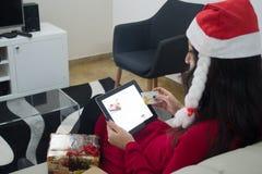 在沙发的圣诞老人圣诞节妇女网上购物 免版税库存照片