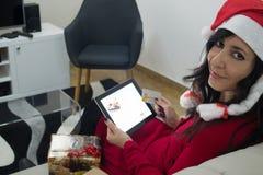 在沙发的圣诞老人圣诞节妇女网上购物 库存图片