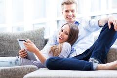在沙发的夫妇有数字式片剂的 免版税库存图片