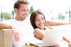 在沙发的夫妇有笑膝上型计算机的个人计算机的在家 库存图片