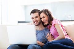 在沙发的夫妇有膝上型计算机的 免版税库存图片