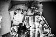 在沙发的好的白种人夫人睡眠有保护她的她的两条哈巴狗狗的 免版税库存照片