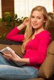在沙发的妇女舒适的开会和使用片剂计算机 免版税图库摄影