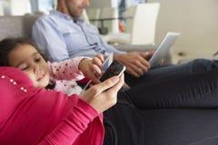 在沙发的家庭有智能手机、膝上型计算机和数字式片剂的 库存照片