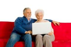 在沙发的年长夫妇使用膝上型计算机 免版税库存图片