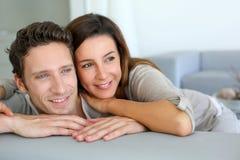 在沙发的微笑的夫妇 免版税库存照片