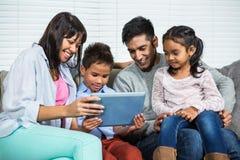 在沙发的微笑的家庭使用片剂 库存图片