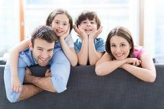 在沙发的微笑的家庭 库存照片