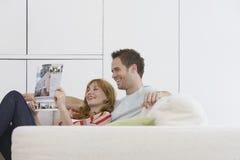 在沙发的快乐和轻松的夫妇读书小册子 免版税库存照片