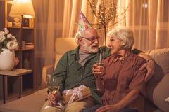 在沙发的快乐的夫妇品尝酒精 库存图片