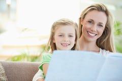 在沙发的母亲和女儿读书 免版税库存照片