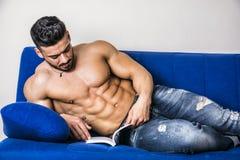 在沙发的男性爱好健美者阅读书 免版税库存照片