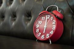 在沙发的红色减速火箭的闹钟 库存照片