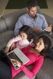 在沙发的西班牙家庭使用膝上型计算机和数字式片剂 免版税图库摄影