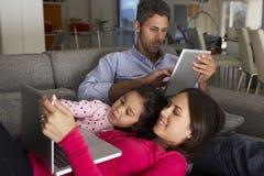 在沙发的西班牙家庭使用膝上型计算机和数字式片剂 库存照片