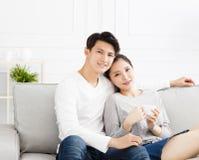 在沙发的轻松的年轻夫妇 免版税库存照片