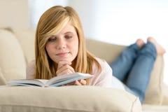 在沙发的年轻学生女孩阅读书 免版税库存照片
