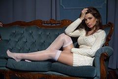 在沙发的年轻有吸引力的深色的妇女就座 库存图片