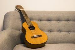 在沙发的Guitarlele 免版税图库摄影