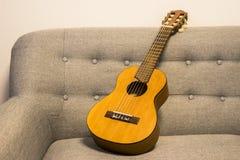 在沙发的Guitarlele 库存图片