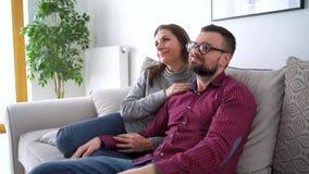 在沙发看电视一起接受的愉快的夫妇在新房和电影里 概念:休闲 股票录像