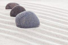 在沙子、温泉或者禅宗概念的三块石头 库存图片
