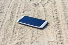 在沙子丢失的智能手机 库存照片