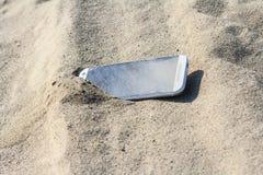 在沙子丢失的智能手机 图库摄影