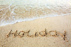 在沙子写的假日在海滩 库存图片
