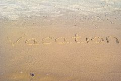 在沙子写的假期 免版税库存图片
