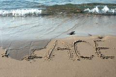在沙子写的和平 免版税图库摄影