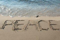 在沙子写的和平 免版税库存图片