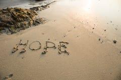 在沙子写的希望在海滩在背景中挥动 库存图片