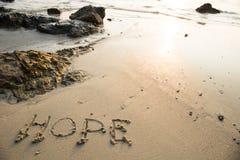 在沙子写的希望在海滩在背景中挥动 免版税库存照片