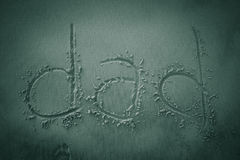 在沙子写的爸爸 免版税库存图片