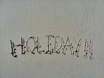 在沙子写的词假日在海滩在岸 免版税库存照片