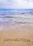在沙子写的连接词,与波浪在背景 免版税库存照片