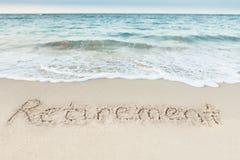 在沙子写的退休由海 免版税库存照片