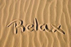 在沙子写Relax 免版税库存图片