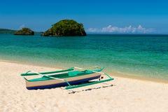 在沙子和两个小海岛的Fishboat在热带绿松石海 库存图片