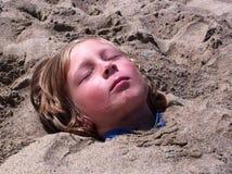 在沙子和取暖埋葬的男孩在阳光下 库存图片